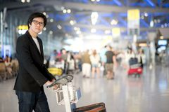Young asian man with luggage in airport terminal Royalty Free Stock Photo