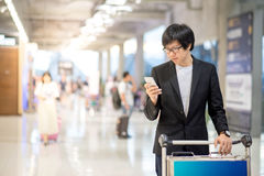 Young asian man using smartphone in airport terminal Stock Photo