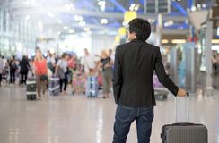 Young asian man with luggage in airport terminal Royalty Free Stock Image