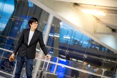 Young asian man with luggage in airport terminal Royalty Free Stock Photography