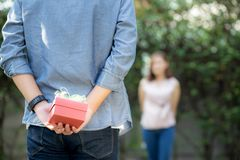 Young asian man holding behind back gift box surprise girlfriend excited in the garden with happy, anniversary day of couple. Young asian men holding behind back stock photos