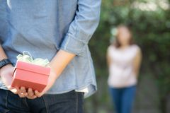 Young asian man holding behind back gift box surprise girlfriend excited in the garden with happy, anniversary day of couple. Young asian men holding behind back stock photography
