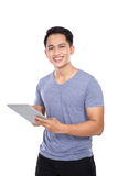 Young Asian man holding a digital touch screen tablet computer o. A portrait of a young asian man holding a digital touch screen tablet computer on white stock photos