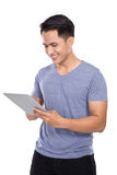 Young Asian man holding a digital touch screen tablet computer o. A portrait of a young asian man holding a digital touch screen tablet computer on white stock images