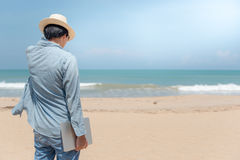 Young Asian man holding laptop on the beach Royalty Free Stock Photography