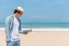 Young Asian man holding laptop on the beach royalty free stock image
