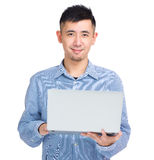 Young asian man holding laptop computer Stock Images