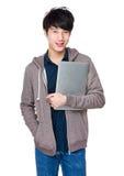 Young asian man holding laptop computer Stock Photo