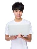 Young asian man holding laptop computer Stock Photos