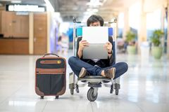 Young asian man holding laptop on airport trolley Royalty Free Stock Image