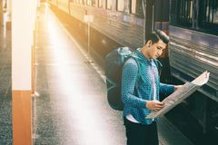 Young asian man holding map paper and looking route with plan fo. R travel Stock Photo