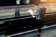 Young asian man holding map paper and looking route with plan fo. R travel Royalty Free Stock Image
