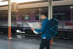 Young asian man holding map paper and looking route with plan for travel.  stock photo