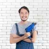 Young Asian man holding power drill standing in front white brick wall, smiling and looking at camera, concept for home DIY royalty free stock images
