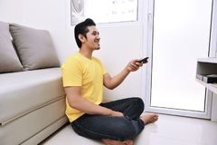 Young asian man holding remote control watching tv while sitting Stock Photo