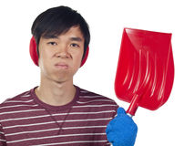 Young Asian man holding snow shovel Stock Image