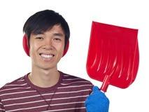 Young Asian man holding snow shovel Stock Photo