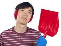 Young Asian man holding snow shovel Royalty Free Stock Photo