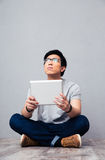 Young asian man holding tablet computer Stock Photography
