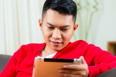 Young Asian man at home on the sofa Stock Photos