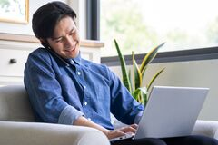 Free Young Asian Man Is Calling While Using Computer Royalty Free Stock Photography - 216672107