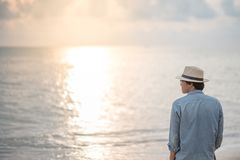 Young Asian man on the beach looking beautiful sunset. Young Asian man with jean shirt and hat standing on the beach and looking beautiful sunset, vacation time Stock Image