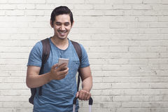 Young asian man journey with mobile phone carrying suitcase. Against white wall background Stock Photo