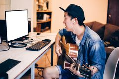 Young Asian man learning how to play guitar on computer monitor. Male guitarist watching online tutorial. Include clipping path. On monitor Royalty Free Stock Photography