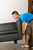 Young asian man lifting a couch Royalty Free Stock Images