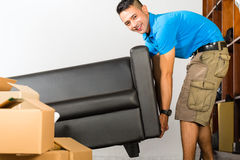 Young asian man lifting a couch Royalty Free Stock Image