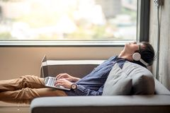 Young asian man listening to music from laptop computer. Young asian man enjoy listening to music from laptop computer with headphones on sofa, urban lifestyle Royalty Free Stock Image