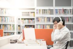 Young Asian man listening to music in library Stock Image