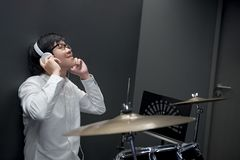 Young Asian man listening to music in music practice room Stock Photography