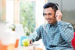 Young Asian man listening and watching an online video Royalty Free Stock Images