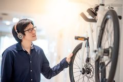Young Asian man looking for bicycle in bike shop stock images