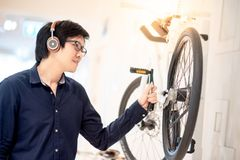 Young Asian man looking for bicycle in bike shop stock image