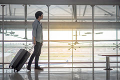 Young Asian man with luggage in airport terminal. Young Asian man walking in the airport terminal with suitcase luggage, travel lifestyle Royalty Free Stock Photo