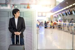 Young asian man with luggage in airport terminal Royalty Free Stock Photos
