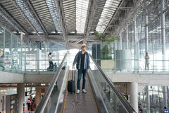 Young Asian man with luggage down the escalator in airport. Stock Photos