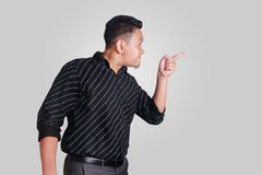 Young Asian Man Mad and Pointing. Side view portrait of young Asian man, angry mad boss pointing,  on grey Royalty Free Stock Images