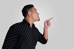 Young Asian Man Mad and Pointing. Side view portrait of young Asian man, angry mad boss pointing,  on grey Royalty Free Stock Photography
