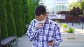 Young asian man with a medical mask on the face coughing and he uses a smartphone stock footage