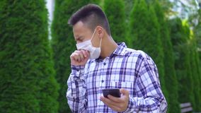 Young asian man in a medical mask on his face goes through the park coughing and uses a smartphone slow mo stock video footage