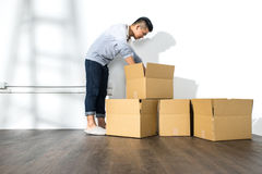 Young asian man moving house Packing cardboard using adhesive Stock Image