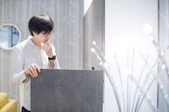 Young Asian man opening modern wardrobe choosing furniture in wa. Rehouse. Home decoration shopping concept Royalty Free Stock Photography
