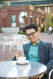 Young asian man in outdoor cafe Royalty Free Stock Photo