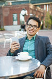 Young asian man in outdoor cafe Royalty Free Stock Images