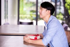 Young Asian man patiently sitting in cafe restaurant and holding a present gift giving to someone special for special occasion. Young Asian man patiently stock photos
