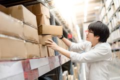 Young Asian man picking paper boxes in warehouse. Young Asian man picking paper box from shelf in warehouse, shopping warehousing or packing products concepts Royalty Free Stock Photo