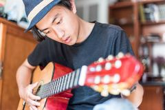 Young asian man playing spanish guitar indoors. royalty free stock photography